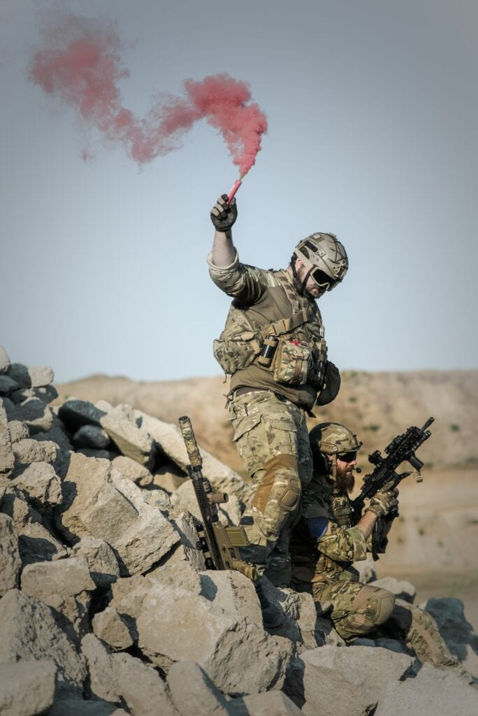 2-soldier-with-guns-on-grey-pile-of-rocks-holding-smoke-163489